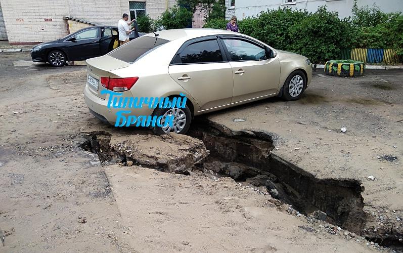 В Брянске под автомобилем во дворе дома образовался провал