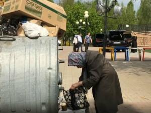 Старушка роется в помойке, рядом батюшка «освящает» джип (видео)